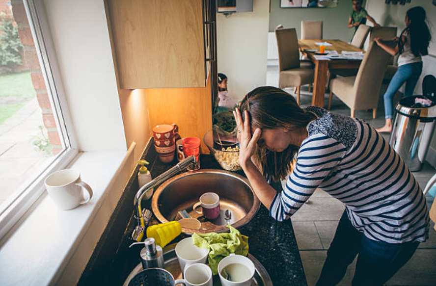femme stressée débordée épuisée enfants charge mentale ménage vaisselle tâche ménagère mère célibataire