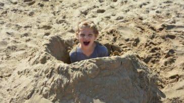 enfant sable enterrer jeu plage